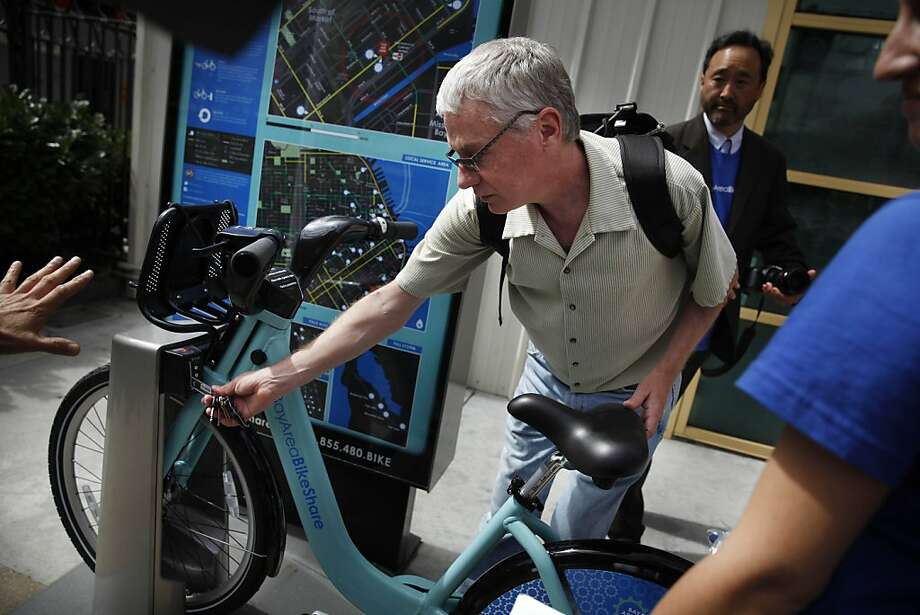 Laura Ruchinskas (partially seen at right) of Alta Bike Share shows Brian Smith of Oakland how to check out a bicycle. Photo: Lea Suzuki, The Chronicle