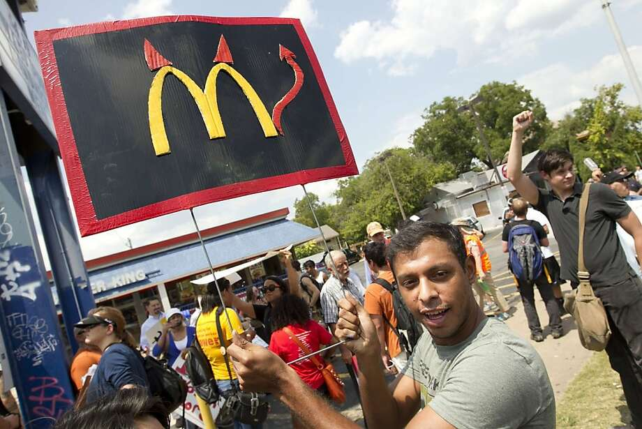 Billions and billions ... enslaved? Those aren't hook 'em horns Danny Alvarez has added to the Golden Arches in Austin, Texas. Alvarez was one of about 200 supporters rallying for striking fast-food workers. Photo: Jay Janner, McClatchy-Tribune News Service