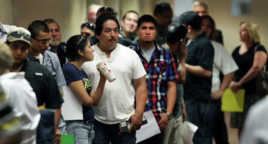 Men and women looking for work stand in line at a job fair. Texas policymakers should realize that taking good care of workers is also good for the long-term business climate. Photo: File Photo, SanAntonio Express-News