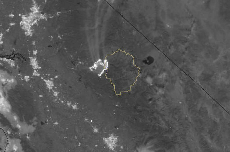 This nighttime photo of the Rim Fire was taken on Aug. 23 via the Visible Infrared Imaging Radiometer Suite on the Suomi NPP satellite.  In the picture, you can see the fire was actually brighter than the lights from nearby metropolitan areas.  The yellow line indicates the boundaries of Yosemite National Park. (NASA)