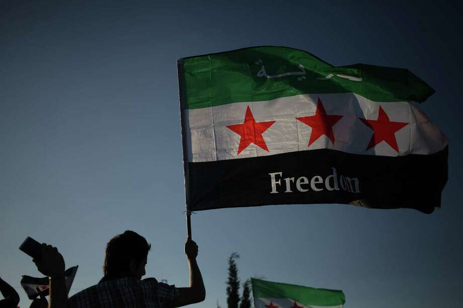 A protester waves the Syrian revolutionary flag in Amman, Jordan, to condemn the alleged poison gas attack.  A reader says it would be a grave mistake to get involved in the Syrian conflict. Photo: Mohammad Hannon / Associated Press