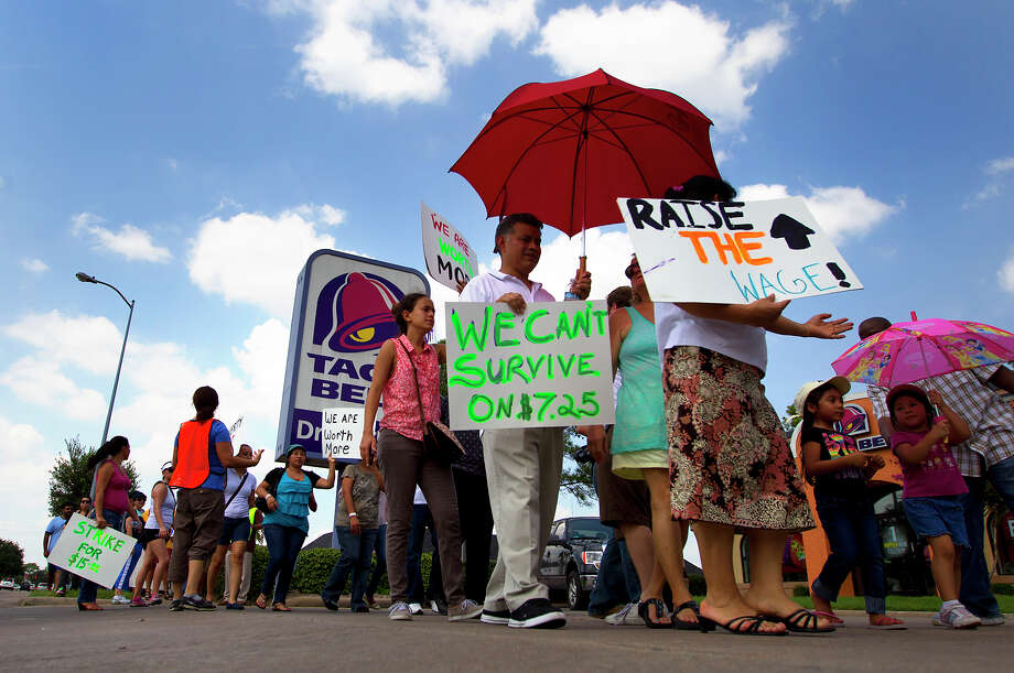 Protestors walk in front of Taco Bell on Richmond Avenue to protest wages paid to fast food employees,Thursday, Aug. 29, 2013, in Houston. Protestors joined the national movement to try and increase minimum wage to $15 per hour for fast food employees. Photo: Cody Duty, Houston Chronicle / © 2013 Houston Chronicle