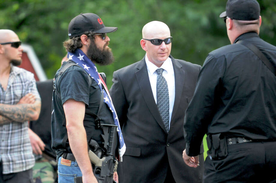 Gilberton Police Chief Mark Kessler, center, talks with members of his Constitutional Security Force outside Borough Hall before a council meeting in Gilberton, Pa.  The city fathers may decide to fire him Friday. Photo: Jacqueline Dormer, MBR / Republican-Herald