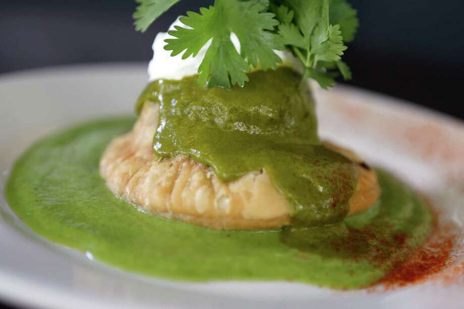 A creamy and spicy poblano sauce surrounds a tender pastry that encases braised short rib meat in the Big Red empanada. Photo: William Luther / San Antonio Express-News