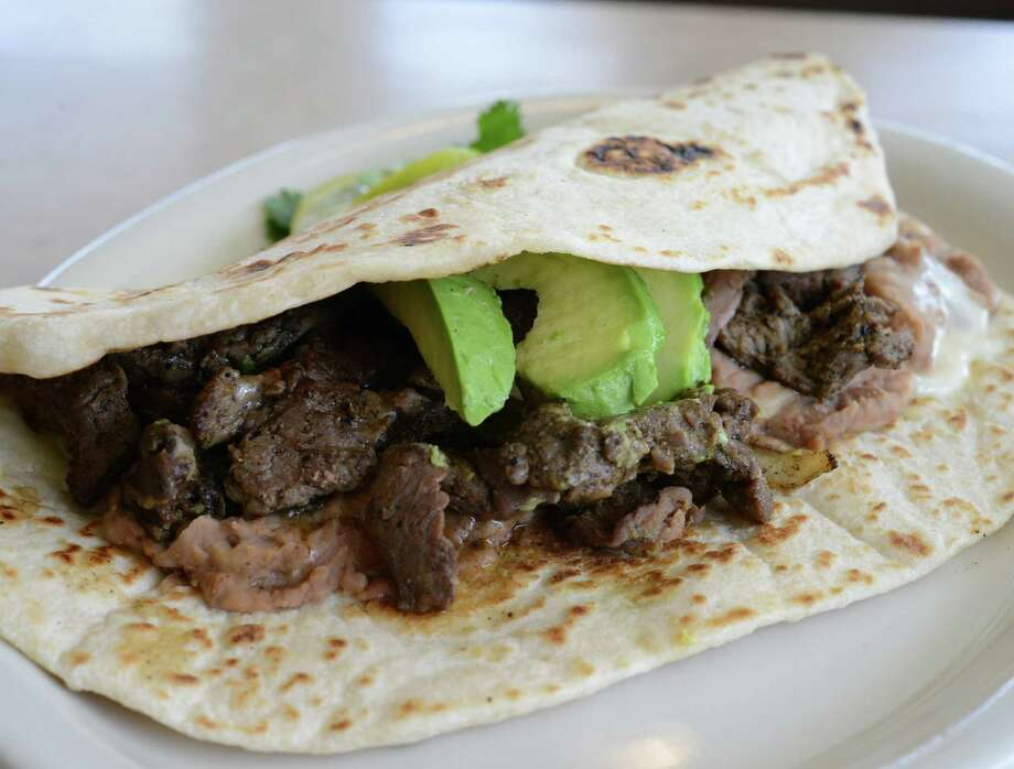 At its best, Taco Norteño is stuffed with meat, grilled onions and peppers, beans and cheese — and bursting with flavor. Photo: Photos By Billy Calzada / San Antonio Express-News