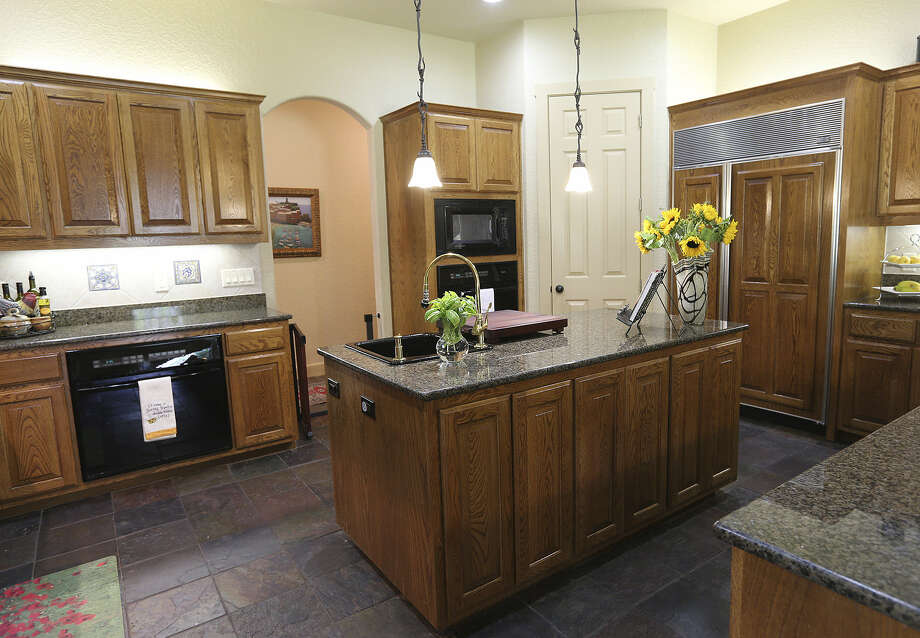 Granite countertops and warm wood tones create an inviting atmosphere.