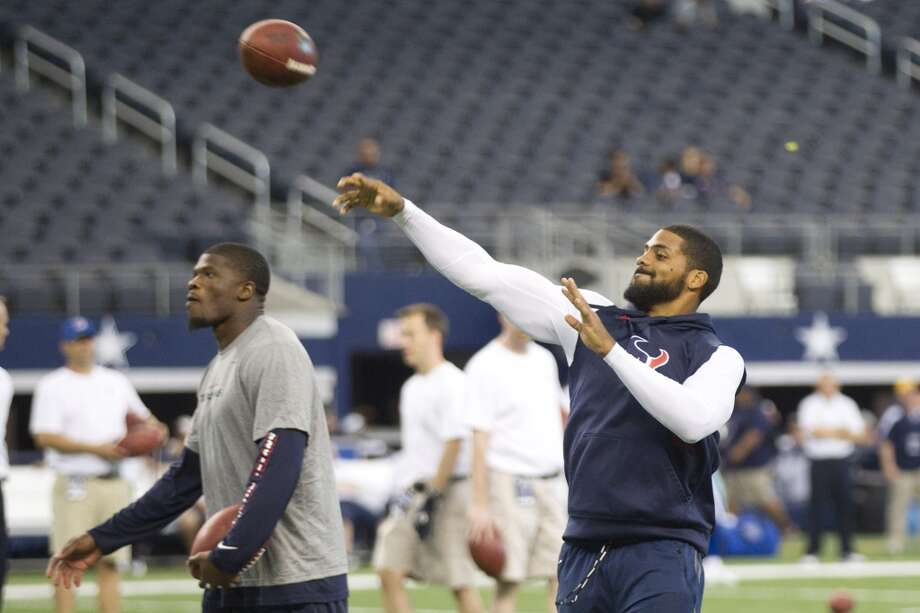 Texans running back Arian Foster throws a football, with receiver Andre Johnson, left, before the game. Photo: Brett Coomer, Houston Chronicle