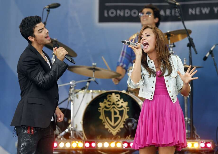 "Joe Jonas, left, and Nick Jonas, on drums, of The Jonas Brothers, perform with Demi Lovato during ABC's ""Good Morning America"" television program Friday, Aug. 13, 2010, in New York. Photo: Jason DeCrow, AP"