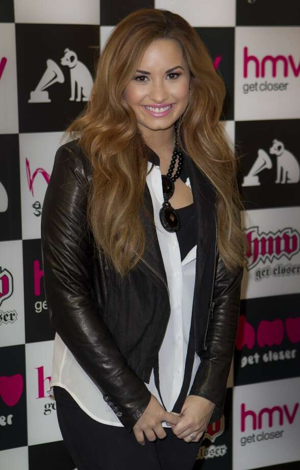 US singer Demi Lovato poses for photographs before she meets fans and signs copies of her new album, 'Unbroken', at a central London music store, Tuesday, April 3, 2012. Photo: Joel Ryan, AP