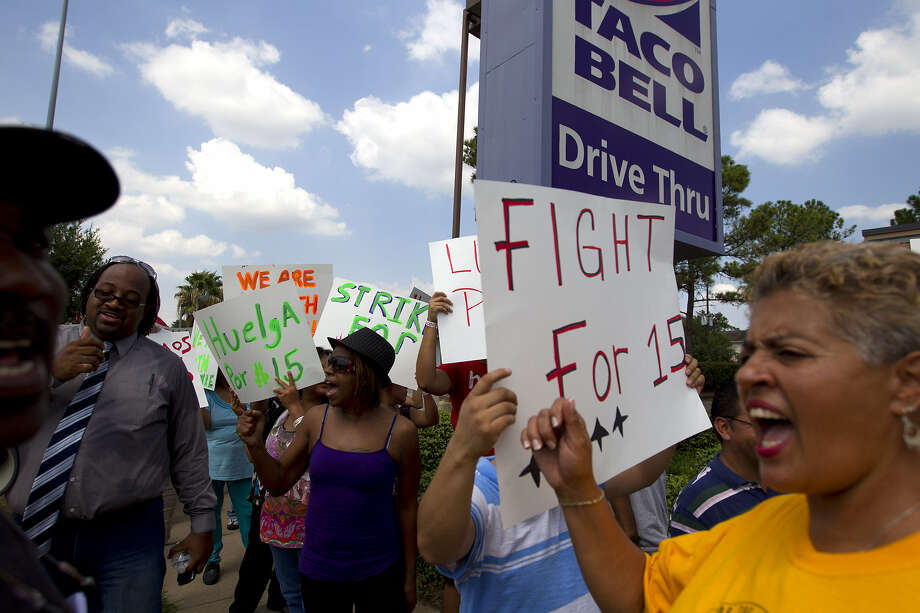 Protesters rally in front of Taco Bell in Houston to protest wages paid to fast food employees.  Protesters joined a national movement to try to get an increase in minimum wage to $15 per hour for fast food employees. Photo: Photos By Cody Duty / Houston Chronicle