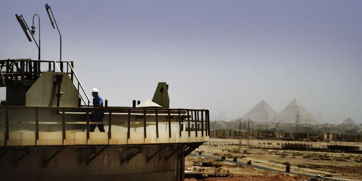 Qarun Petroleum Company's oil shipping tanks at Dashour with the Giza pyramids as a backdrop. Qarun Petroleum is an Apache joint venture in Egypt.