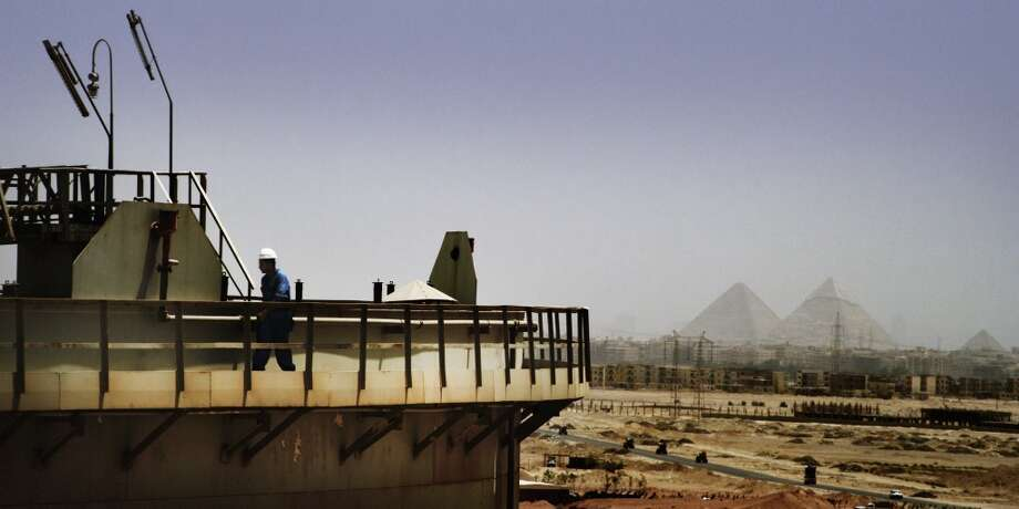 Qarun Petroleum Company's oil shipping tanks at Dashour with the Giza pyramids as a backdrop. Qarun Petroleum is an Apache joint venture in Egypt. Photo: Apache Corp.
