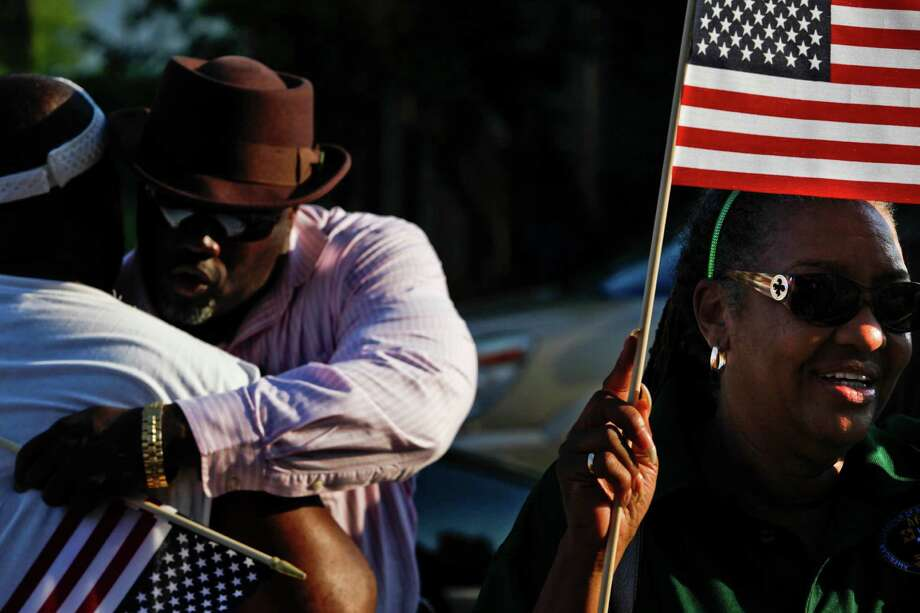 "Sharon Holmes, right, holds a flag as Galveston community groups march on the 50th anniversary of Martin Luther King's ""I had a dream"" speech to protest the failure to rebuild public housing five years after Hurricane Ike August 29, 2013 in Galveston, TX. The march ended at Avenue L Missionary Baptist Church at 2612 Avenue L to hear community leaders and clergy speak about housing and civil rights issues. Photo: Eric Kayne, For The Chronicle / ©Eric Kayne 2013"