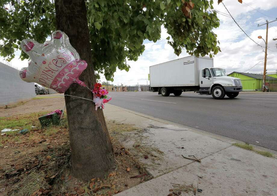 A balloon is tied to a tree next to the pole that was struck by a car driven by the 8-year-old brother of Aaliyah Felder in Phoenix. Aaliyah, 6, died. Photo: Matt York / Associated Press