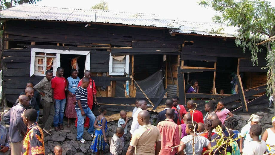 Onlookers gather around a house damaged by overnight shelling in Goma, eastern Congo. Photo: Alain Wandimoyi / Associated Press