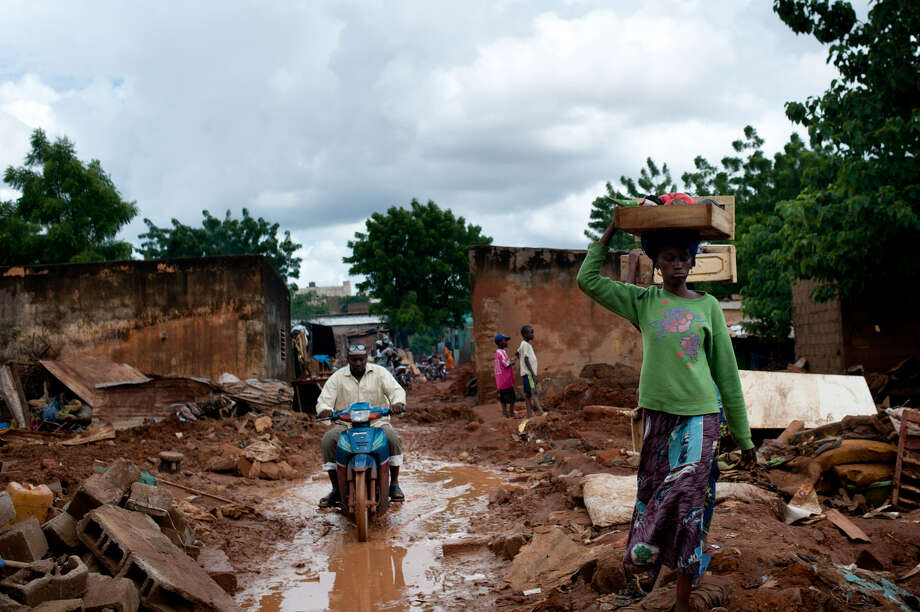 A woman carries what is left of her belongings after flooding caused many houses to collapse in the Banconi neighborhood of Bamako, Mali. Photo: Emilie Regnier / Associated Press