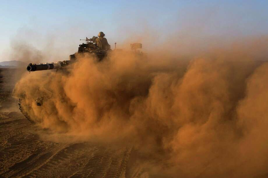 Israeli soldiers on Thursday drive a tank through a staging area in the Golan Heights, near the border of Syria. Israel is preparing for possible Syrian attacks. Photo: Bernat Armangue, STF / AP