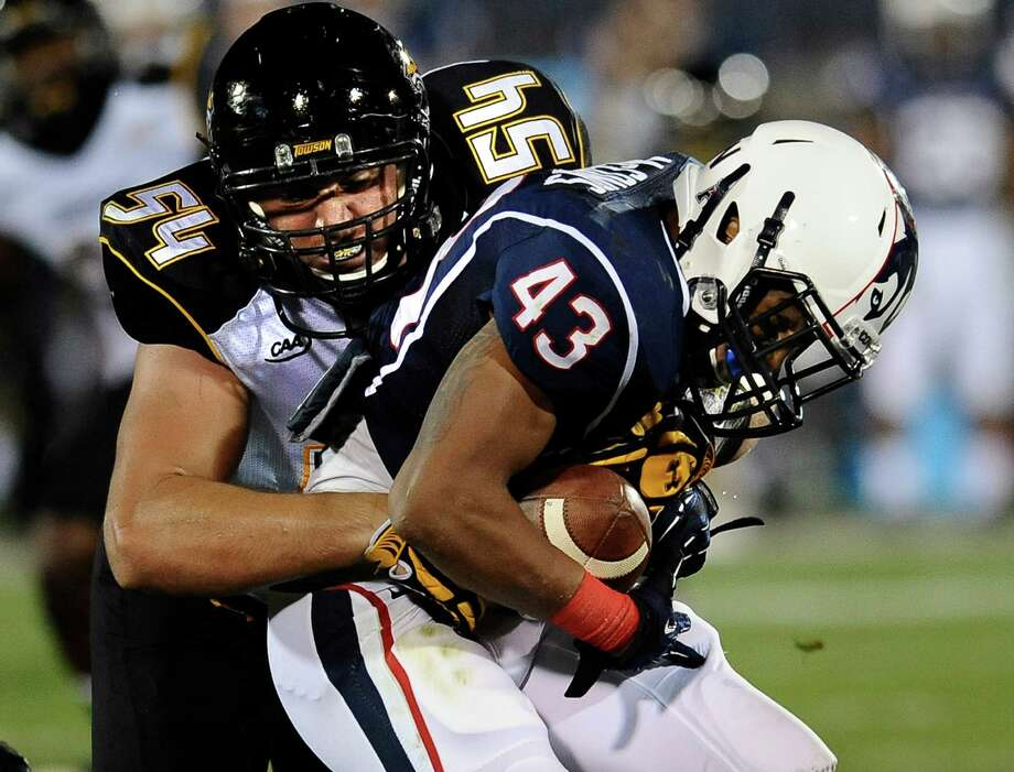 Towson defensive end Drew Cheripko (54) tackles Connecticut running back Lyle McCombs (43) during the first half of an NCAA college football game at Rentschler Field in East Hartford, Conn., Thursday, Aug. 29, 2013. Photo: Jessica Hill, AP / Associated Press