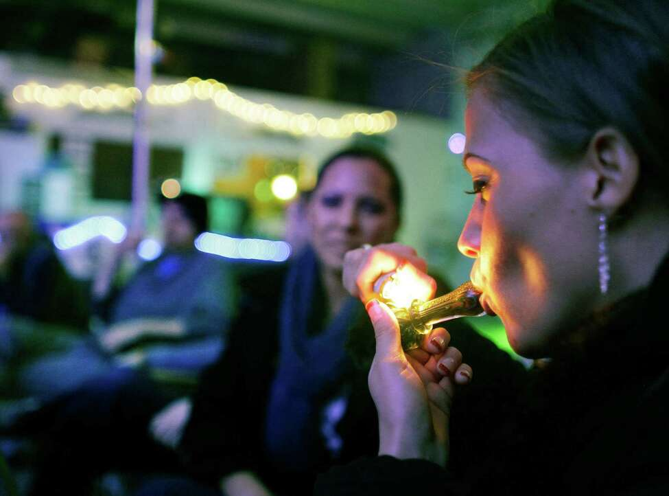 FILE - In this in Dec. 31, 2012 file photo, Rachel Schaefer of Denver smokes marijuana on the official opening night of Club 64, a marijuana-specific social club, where a New Year's Eve party was held, in Denver. According to new guidance being issued Thursday, Aug. 29, 2013 to federal prosecutors across the country, the federal government will not make it a priority to block marijuana legalization in Colorado or Washington or close down recreational marijuana stores, so long as the stores abide by state regulations. (AP Photo/Brennan Linsley) ORG XMIT: COBL503