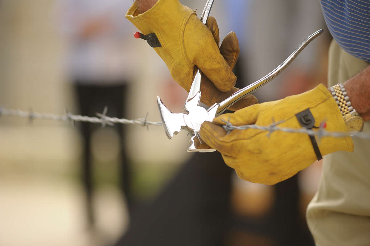 Instead of the usual ribbon cutting, Dr. Charles Wiseman used barbed wire to commemorate the 20th anniversary of the Hyatt Hill Country Resort and Spa Monday.