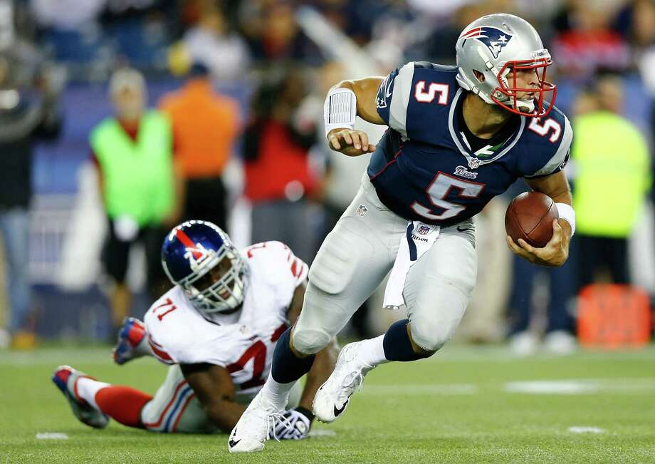 FOXBORO, MA - AUGUST 29: Tim Tebow #5 of the New England Patriots evades a tackle and runs with the ball past Adewale Ojomo #71 of the New York Giants during the preseason game at Gillette Stadium on August 29, 2013 in Foxboro, Massachusetts. (Photo by Jared Wickerham/Getty Images) ORG XMIT: 173355147 Photo: Jared Wickerham / 2013 Getty Images