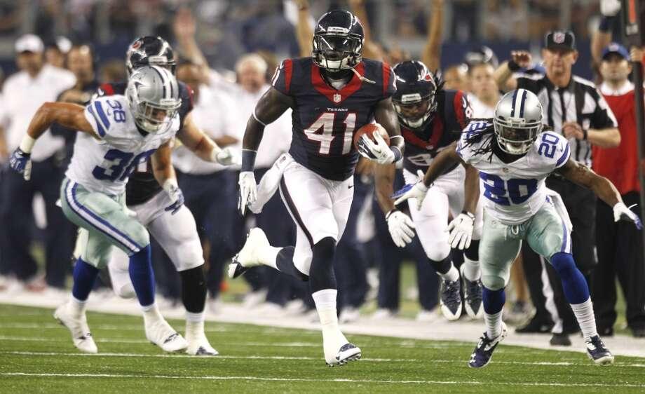 Texans running back Cierre Wood breaks away between Cowboys defensive backs Jeff Heath and B.W. Webb. Photo: Brett Coomer, Houston Chronicle