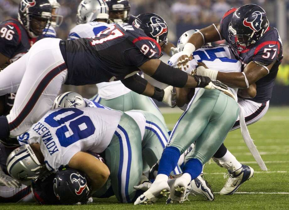Texans defensive tackle Terrell McClain and linebacker Sam Montgomery tackle Cowboys running back Joseph Randle at the line of scrimmage. Photo: Brett Coomer, Houston Chronicle