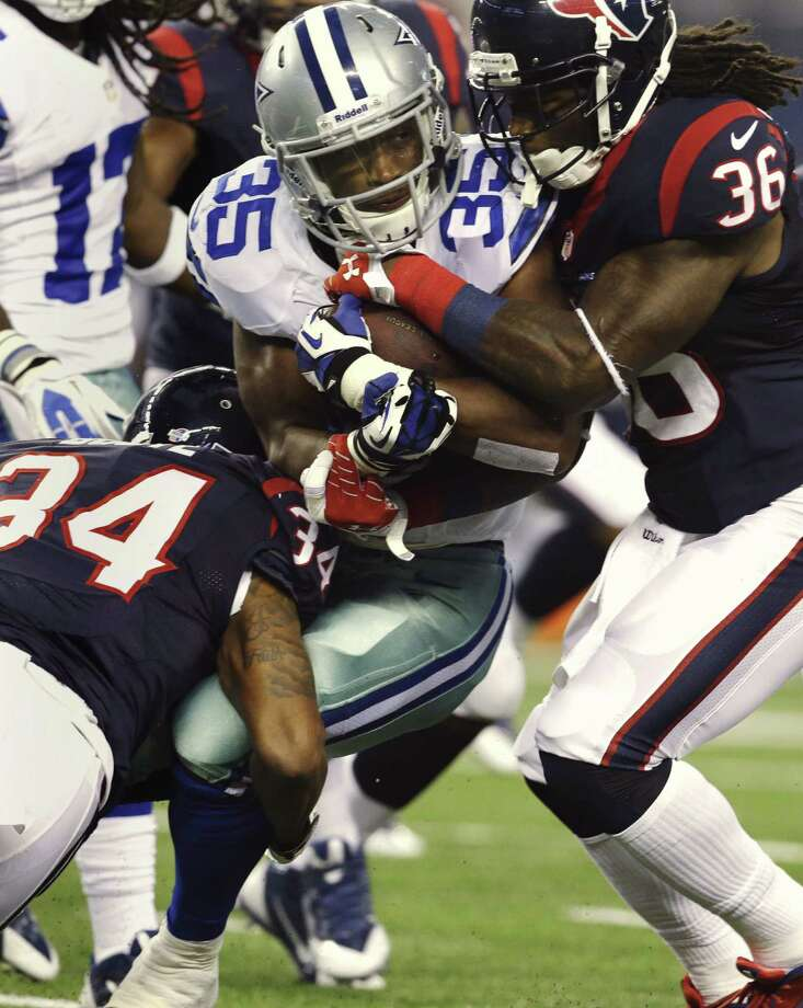 Cowboys running back Joseph Randle is swarmed by Texans A.J. Bouye (left) and D.J. Swearinger in the first half. Photo: LM Otero / Associated Press