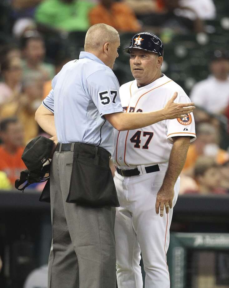 Astros third base coach Dave Trembley talks with home plate umpire Mike Everitt after Robbie Grossman struck out to end the third inning. Photo: Karen Warren, Houston Chronicle