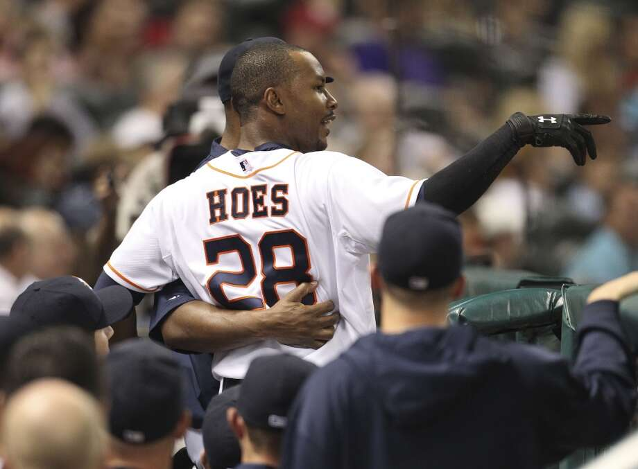 Astros right fielder L.J. Hoes stops in the dugout to chat with Bo Porter after he scored on an RBI double by Jason Castro. Photo: Karen Warren, Houston Chronicle