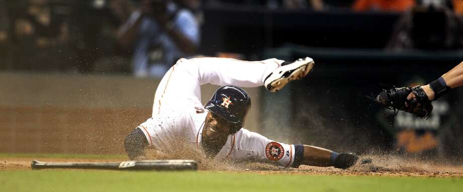 L.J. Hoes dives into home for a run on an RBI double by Jason Castro. Photo: Karen Warren, Associated Press