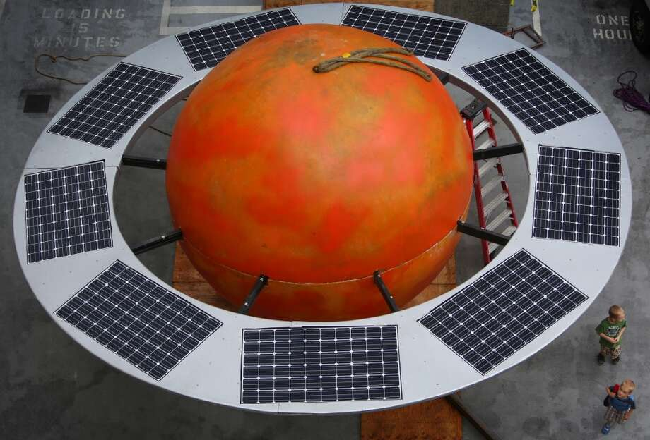 "Children look over the orange sphere as a 12 foot-tall fiberglass replica of the planet Saturn is readied to be installed on the roof of Fremont's Saturn Building on Thursday, August 29, 2013. The large orange orb, complete with a ring of solar panels, was installed across the street from the Fremont rocket, in the ""center of the universe."" Photo: JOSHUA TRUJILLO, SEATTLEPI.COM"