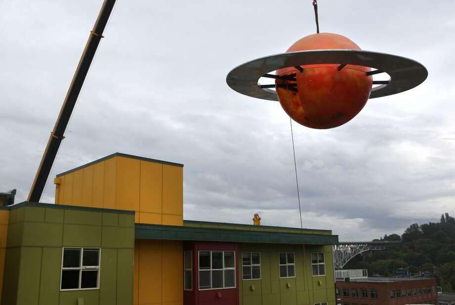 A crane hoists a 12 foot-tall fiberglass replica of the planet Saturn. Photo: JOSHUA TRUJILLO, SEATTLEPI.COM
