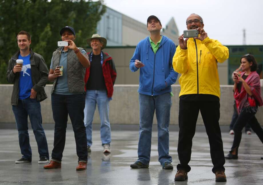 Spectators watch as a 12 foot-tall fiberglass replica of the planet Saturn is installed on the roof of Fremont's Saturn Building. Photo: JOSHUA TRUJILLO, SEATTLEPI.COM