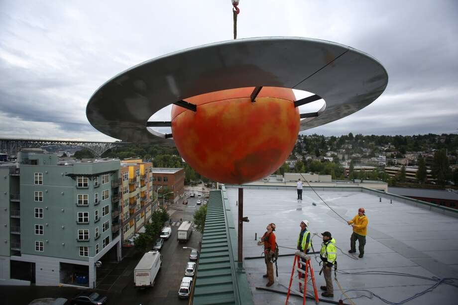 A crew lowers a 12 foot-tall fiberglass replica of the planet Saturn onto Fremont's Saturn Building. Photo: JOSHUA TRUJILLO, SEATTLEPI.COM