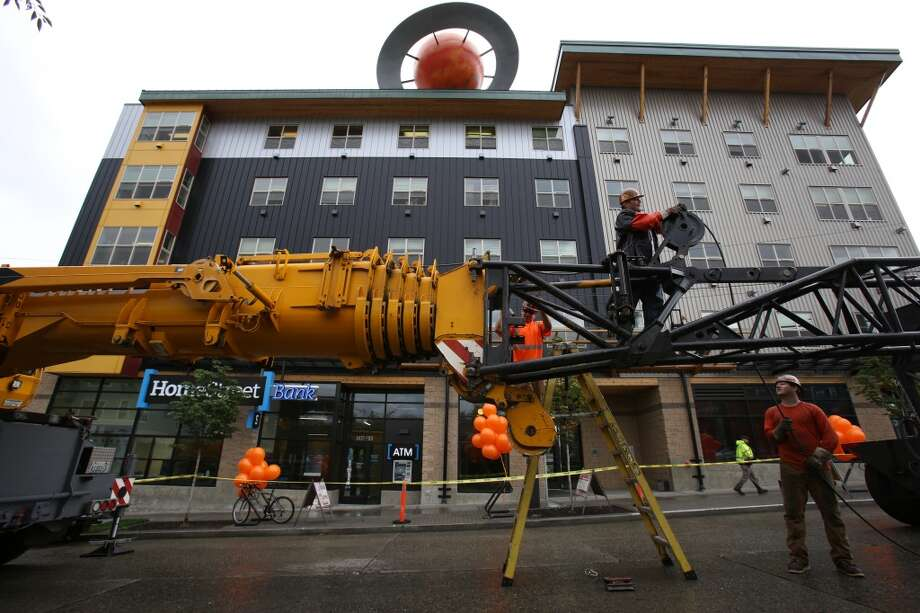 A crane crew works as a 12 foot-tall fiberglass replica of the planet Saturn is installed. Photo: JOSHUA TRUJILLO, SEATTLEPI.COM