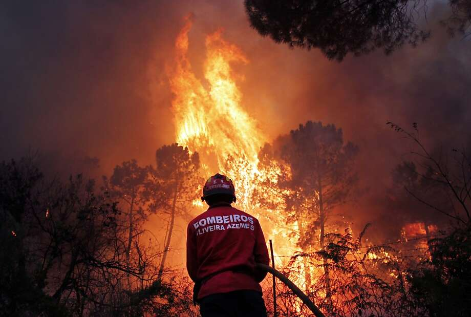 A Portuguese firefighter works to extinguish a wildfire near Caramulo, north Portugal, Thursday, Aug. 29, 2013. Portuguese officials said a woman firefighter died in a forest blaze, becoming the fifth fatality among emergency crews in a month as summer wildfires scorch large areas of parched countryside. (AP Photo/Francisco Seco) Photo: Francisco Seco, Associated Press