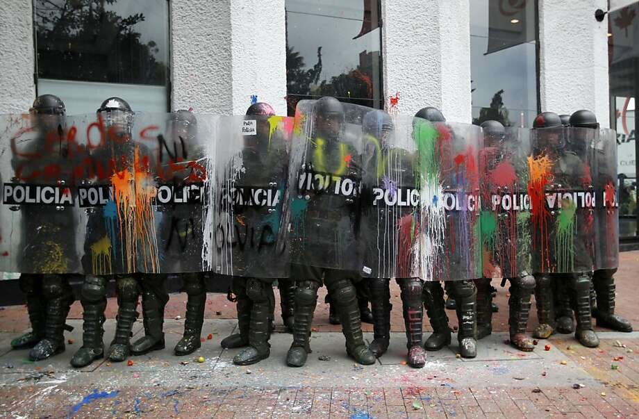 Riot police holding shields covered with paint thrown by protesters guard a public office in downtown Bogota, Colombia, Thursday, Aug. 29, 2013. Students marched in support of farmers who have been blockading highways for more than 10 days for an assortment of demands that include reduced gasoline prices, increased subsidies and the cancellation of free trade agreements. (AP Photo/Fernando Vergara) Photo: Fernando Vergara, Associated Press