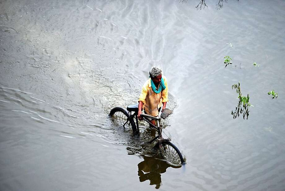 Too deep to ride:A Indian man pushes his bicycle as he wades through floodwater in Allahabad. Many areas in Uttar Pradesh state have been inundated by prolonged monsoon rains. Photo: Sanjay Kanojia, AFP/Getty Images