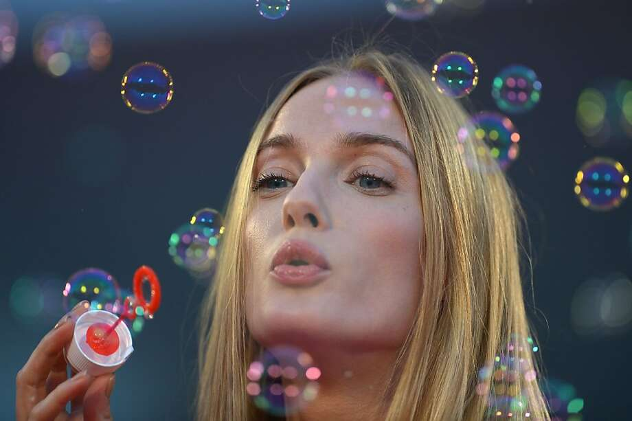 Film buff: Some stars strut on the red carpet and say vacuous things. Italian model Eva Riccobono blows soap bubbles. (Venice Film Festival at Venice Lido.) Photo: Gabriel Bouys, AFP/Getty Images