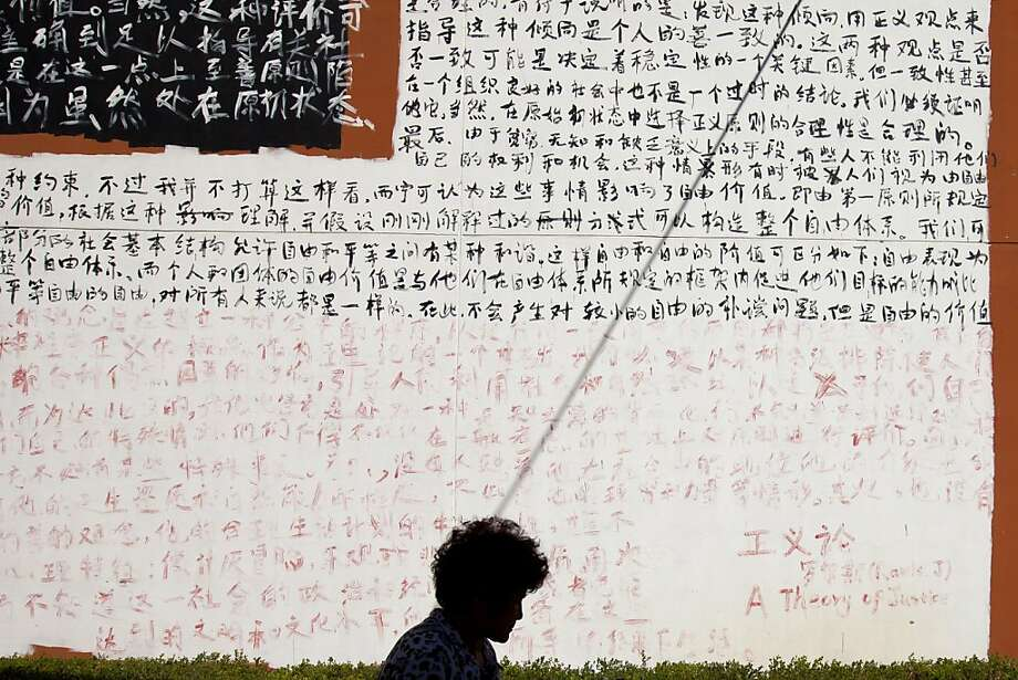 "A woman walks past a wall covered with Chinese characters from chapters of John Rawls' book ""A Theory of Justice"" outside an art gallery in Beijing Thursday, Aug. 29, 2013. An overhead electric wire casts its shadow on the wall. (AP Photo/Alexander F. Yuan) Photo: Alexander F. Yuan, Associated Press"