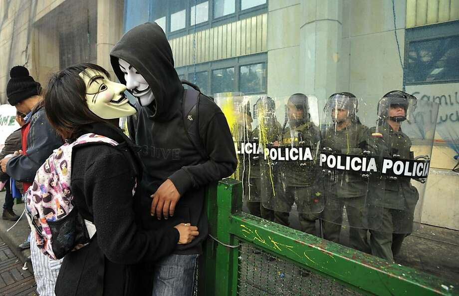 A couple of masked protesters stand near riot police guarding a public building during a rally in Bogota, Colombia, Thursday, Aug. 29, 2013. Students are protesting in support of farmers who demand lower fertilizer prices, complain of being undercut by cheap imports from near and far of products including potatoes, onions and milk, and say their sector is being hurt by free trade and other agreements promoted by the government. (AP Photo/Carlos Julio Martinez) Photo: Carlos Julio Martinez, Associated Press