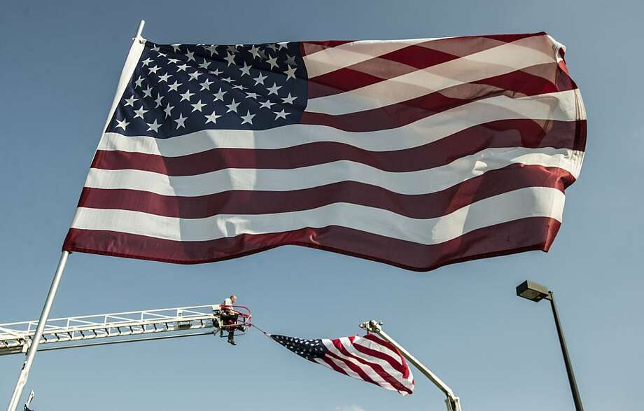 Harrodsburg, KY firefighter Scott Hammons works on hanging a large American flag Thursday, Aug. 29, 2013., at Anderson Dean Park in Harrodsburg, Ky. Hammons was preparing for five days of festivities dubbed The Cost of Freedom Tribute and The Traveling Vietnam Wall. The 370-foot length traveling wall is about six feet in height and has etched upon it the names of more than 58,000 American soldiers who died during the Vietnam conflict. (AP Photo/The Advocate Messenger, Clay Jackson) Photo: Clay Jackson, Associated Press