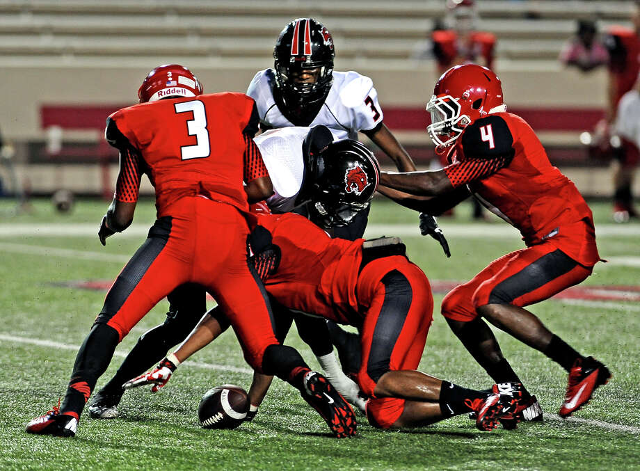 Kirbyville player fumbles the ball after being hit during the Cleveland High School football game against Kirbyville High School at Provost Umphrey Stadium on Thursday, August 29, 2013.  Photo taken: Randy Edwards/The Enterprise @iamrandyedwards Photo: Randy Edwards, Photojournalist / Enterprise