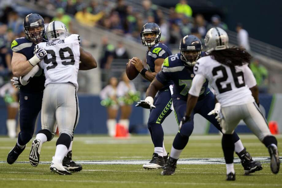 Seahawks quarterback Russell Wilson, background, prepares to throw to a teammate during the first half of the final preseason game Thursday, August 29, 2013, at CenturyLink Field in Seattle. Seahawks led the Raiders 13-3 at the end of the first half. (Jordan Stead, seattlepi.com) Photo: JORDAN STEAD, SEATTLEPI.COM
