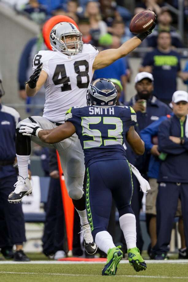 Oakland Raiders player Jeron Mastrud makes a catch over the head of Malcolm Smith during the first half of the final preseason game Thursday, August 29, 2013, at CenturyLink Field in Seattle. Seahawks led the Raiders 13-3 at the end of the first half. (Jordan Stead, seattlepi.com) Photo: JORDAN STEAD, SEATTLEPI.COM