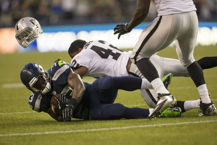 Raiders player Shelton Johnson, middle, loses his helmet in a tackle with Christine Michael, left, during the first half of the final preseason game Thursday, August 29, 2013, at CenturyLink Field in Seattle. Seahawks led the Raiders 13-3 at the end of the first half. (Jordan Stead, seattlepi.com) Photo: JORDAN STEAD, SEATTLEPI.COM