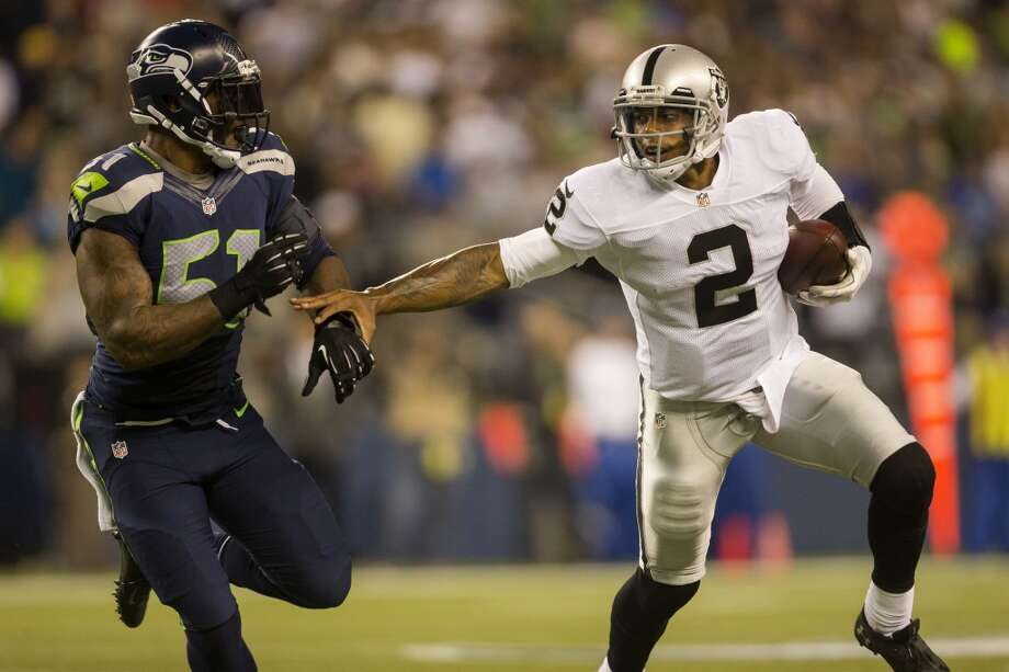 Terrelle Pryor, right, keeps an arm's distance from Bruce Irvin, left, on his way downfield during the first half of the final preseason game Thursday, August 29, 2013, at CenturyLink Field in Seattle. Seahawks led the Raiders 13-3 at the end of the first half. (Jordan Stead, seattlepi.com) Photo: JORDAN STEAD, SEATTLEPI.COM