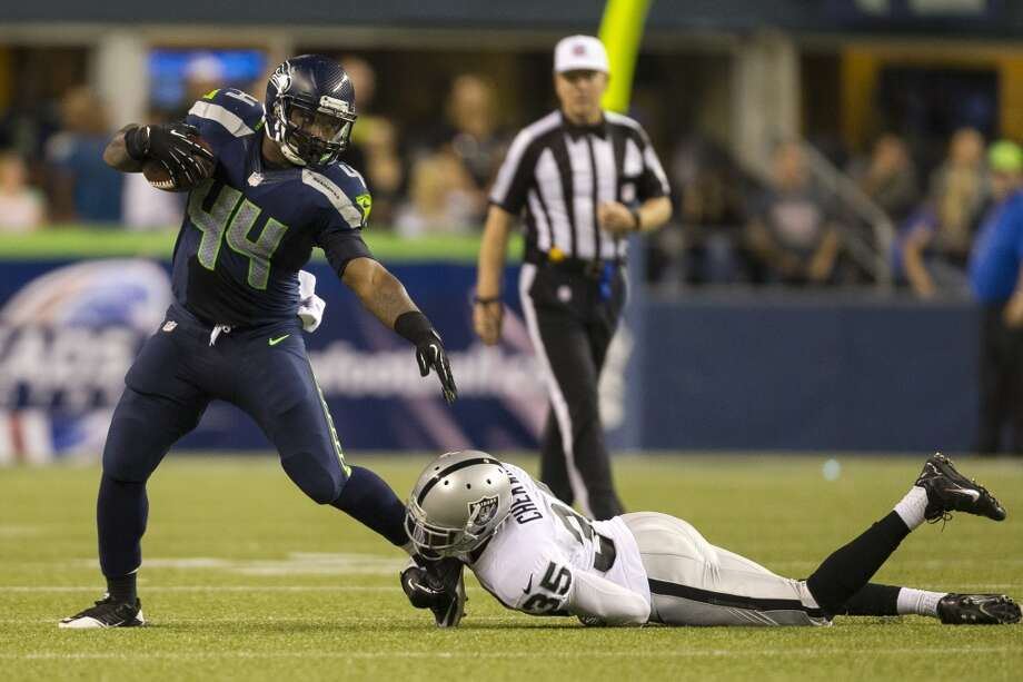 Spencer Ware, left, pulls free from a foot grab by Raiders player Chimdi Chekwa, right, during the second half of the final preseason game Thursday, August 29, 2013, at CenturyLink Field in Seattle. The Seahawks beat the Raiders 22-6. (Jordan Stead, seattlepi.com) Photo: JORDAN STEAD, SEATTLEPI.COM