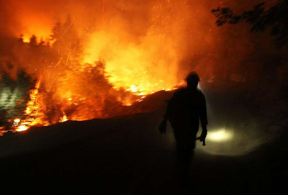 A Hotshot walking the fire line on August 29, 2013.  The wildfire threatening Yosemite National Park is spreading further into the US tourist landmark, officials said as they battled to stop it clouding a holiday weekend. Efforts to contain the so-called Rim Fire, which has grown to become California's sixth biggest wildfire ever, were also being boosted by the deployment of a military drone approved by the Pentagon. The fire, which now covers more than 192,000 acres, or 300 square miles, and is 30 percent contained, has also threatened San Francisco's water supply, due to ash falling on a key reservoir.  Photo: Mike Mcmillan, AFP/Getty Images